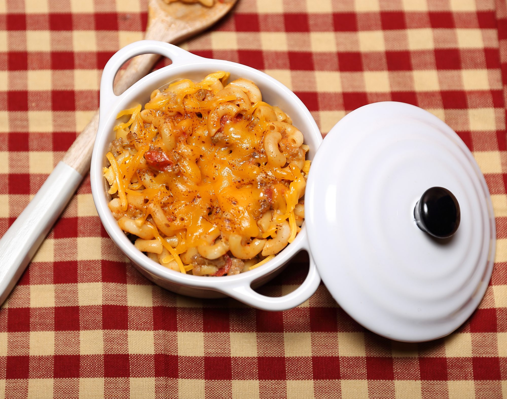 sausage macaroni and cheese on a red and tan checkered tablecloth